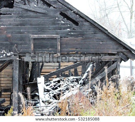 Snowy abandoned burned-out fire wooden black house #532185088