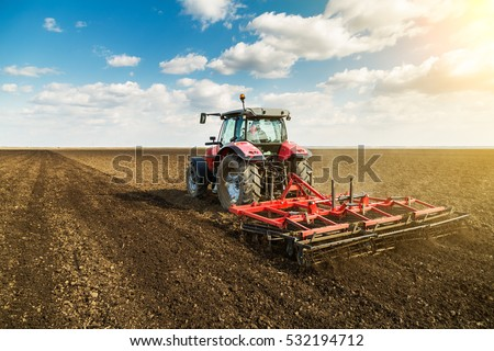Farmer in tractor preparing land with seedbed cultivator as part of pre seeding activities in early spring season of agricultural works at farmlands. #532194712