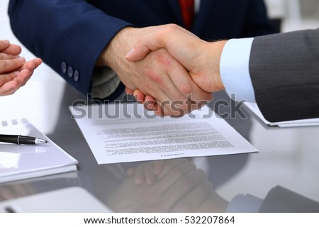 Two business man shaking hands to each other above signed contract #532207864