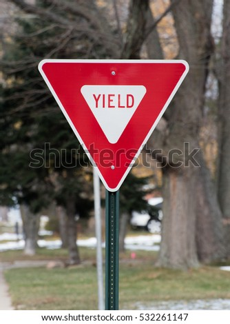 Yield street sign in a city, red triangle traffic roadsign