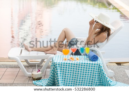 Asian woman with white large summer hat sitting on white pool bench, with cocktaIl near swimming pool #532286800
