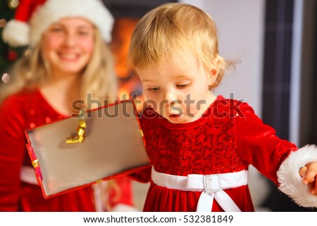little baby girl with santa dress surprised by the content of her christmas gift
