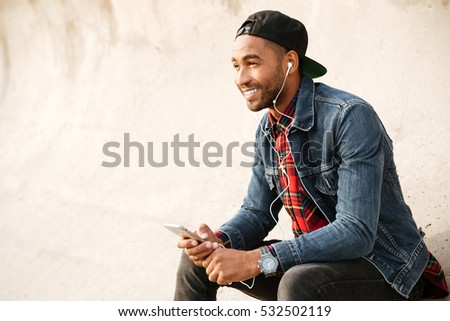 Cheerful african young man wearing cap walking on the beach and chatting by his phone while listening music with earphones. #532502119
