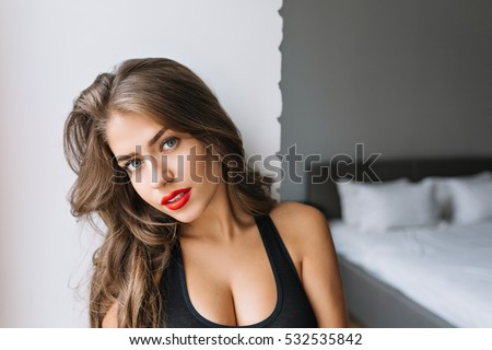 Closeup portrait attractive charming girl with long brunette hair in modern apartment. Sexy T-shirt, true emotion, red lips. Morning, fashionable model, relax