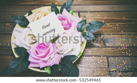 Rose flowers on a plate on a wooden table, a note on the paper good morning