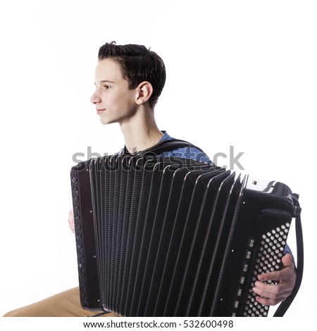 teenage caucasian boy plays the accordion in studio with white background #532600498