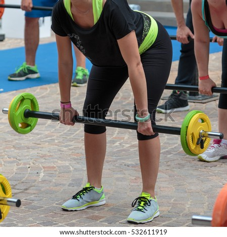Fitness Workout: Pretty Young Girl using Barbell in Gym #532611919