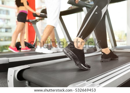 Legs of sporty woman running on treadmill in gym, close up view #532669453