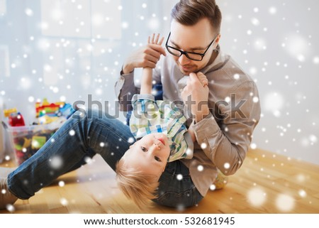 family, childhood, fatherhood, leisure and people concept - happy father and little son playing and having fun at home over snow #532681945