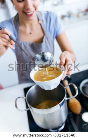 Portrait of young woman serving vegetable soup in the kitchen. #532711540