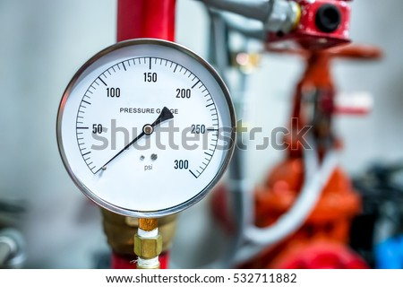 pressure gauge psi meter in pipe and valves of fire emergency system industry focus closeup middle red background #532711882