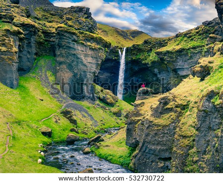 Colorful morning view of Kvernufoss waterfall. Majestic scene in south Iceland with meditating man on the edge of cliff. Artistic style post processed photo. #532730722