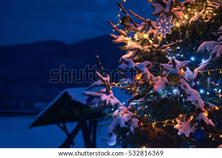 Christmas tree decorated with balls, stars, toys and led electric lights looks like a magic wonder in snowy night mountains landscape