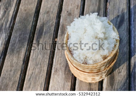 Thai Sticky rice in a kratib made from wicker on wood table #532942312