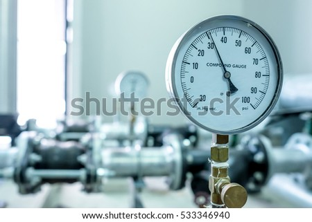 pressure compound gauge psi meter in pipe and valves of water system industrial focus left closeup white light defocus blur background #533346940