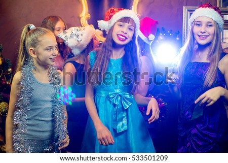 Group of cheerful young girls celebrating Christmas near the Christmas tree with lights #533501209