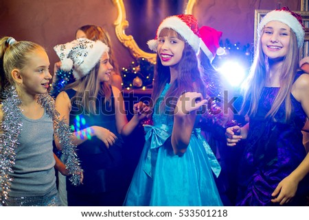 Group of cheerful young girls celebrating Christmas near the Christmas tree with lights #533501218
