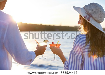 Man and woman holding glasses with margarita cocktail on blurred background #533524417