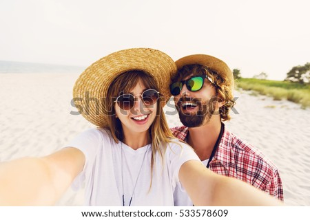 Successful   traveling couple in love taking a selfie on phone at the beach on a sunny summer day. Pretty girl and her handsome boyfriend with beard having fun, crazy emotional faces , laughing.