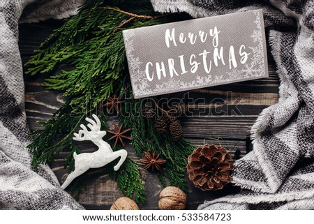 merry christmas text sign on reindeer ornaments with greeting card and fir branches and cones on rustic wooden background. space for text. top view. seasonal greetings concept. winter holidays #533584723