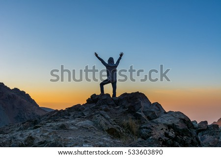 A tourist standing on the peak of a rocky mountain watching sun rising in Darband valley in autumn in dawn against colorful sky in the Tochal mountain.  #533603890