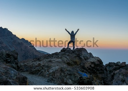 A tourist standing on the peak of a rocky mountain watching sun rising in Darband valley in autumn in dawn against colorful sky in the Tochal mountain.  #533603908