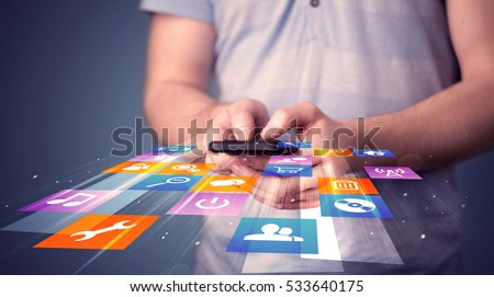 Man holding smart phone with colorful application icons comming out Royalty-Free Stock Photo #533640175