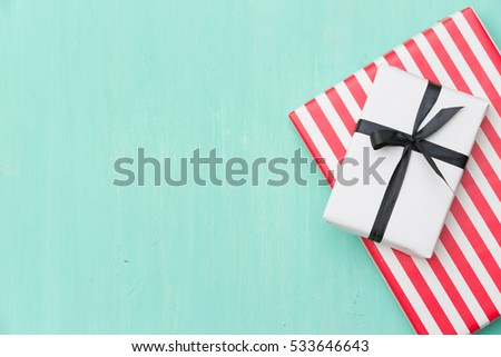 Top view on Christmas gifts wrapped in striped gift paper decorated with ribbon on turquoise wooden background with sparkling stars. New Year, holidays and celebration concept. #533646643