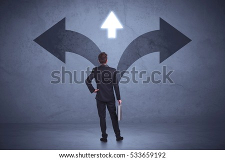 Businessman taking a decision while looking at arrows on the wall concept background #533659192