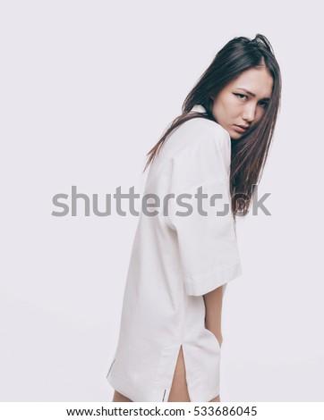 Beautiful expressive asian model in white fashion kimono design dress. Isolated on white. #533686045