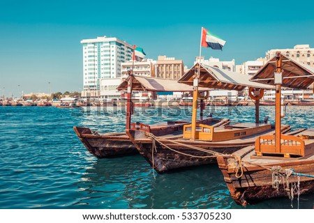 Piers of traditional water taxi boats in Dubai, UAE. Panoramic view on Creek gulf and Deira area. Creative color post processing. Famous tourist destination #533705230