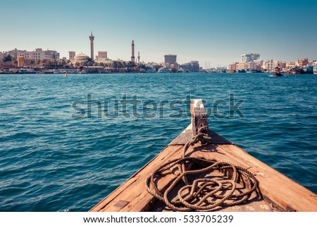 Panoramic view from traditional water taxi boats in Dubai, UAE. Creek gulf and Deira area. United Arab Emirates famous tourist destination. Creative color post processing. #533705239