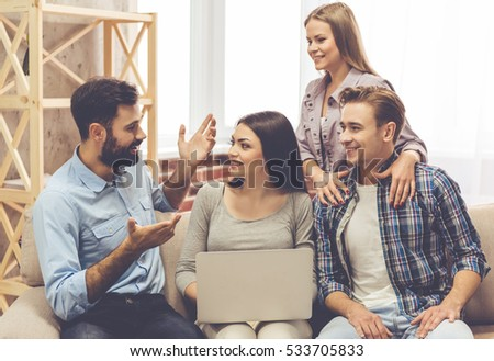 Young people are using a laptop, talking and smiling while spending time together at home #533705833