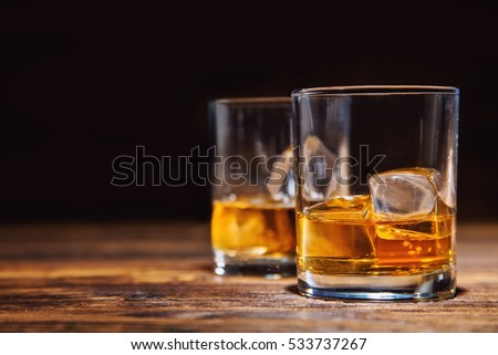 Two glasses of whiskey with ice cubes served on wooden planks. Vintage countertop with highlight and a glass of hard liquor #533737267