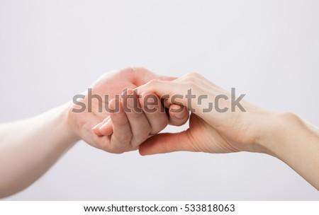 Man's hand gently holding woman's hand - closeup shot #533818063