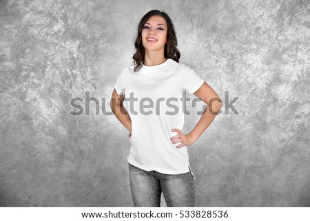 Young woman in blank white t-shirt standing against grey textured wall #533828536