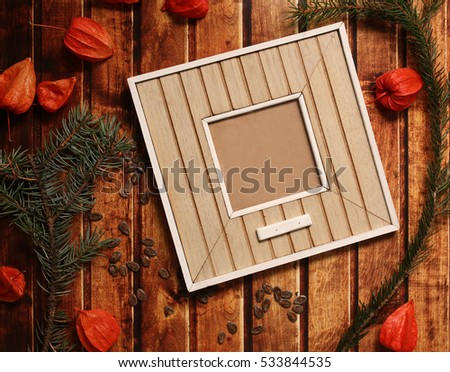 Photo frame stick on vintage wooden texture. Christmas and New Year background concept. frames on retro style table. spruce branches, orange winter cherry and red bowtie