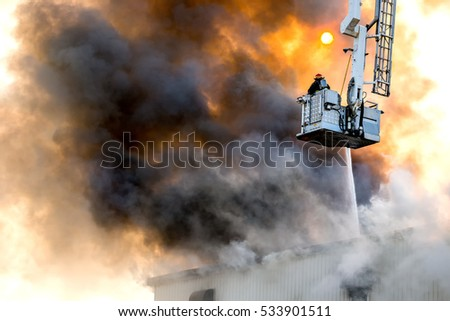Fireman fighting a building fire from bucket above building. A hose sprays water through the smoke. Fireman is wearing breathing apparatus. Thick smoke filled with soot glows orange. Room for text. #533901511