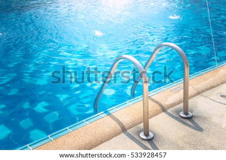 Grab bars ladder in the blue swimming pool Royalty-Free Stock Photo #533928457
