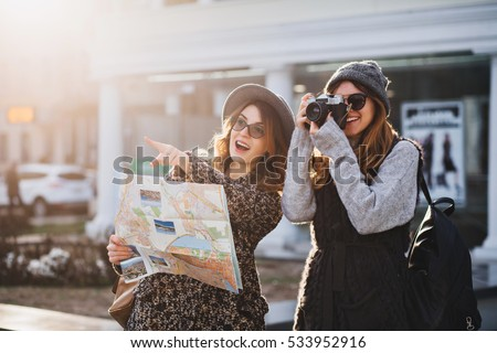 Happy travel together of two fashionable girls in sunny city centre. Young joyful women expressing positivity, using map, vacation with bags, camera, making photo, cheerful emotions, great mood #533952916