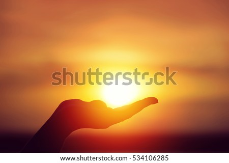 Sun on female hand. Silhouette of hand holding sun  #534106285