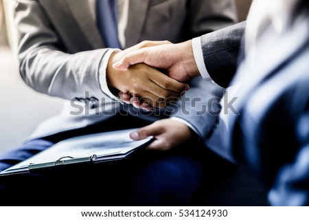 businessman shaking hands to seal a deal with his partner Royalty-Free Stock Photo #534124930