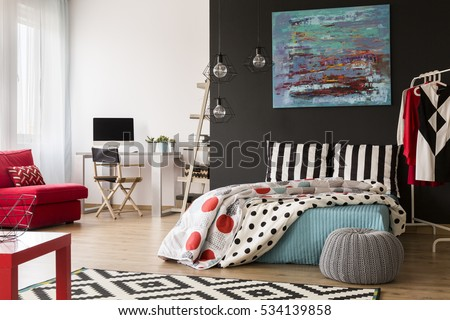 Cozy modern studio with red and blue accessories and bed #534139858