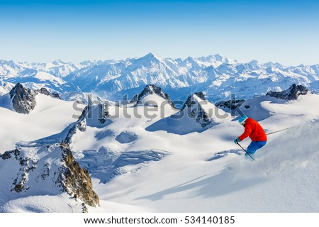 Skier skiing downhill Valle Blanche in french Alps in fresh powder snow. Snow mountain range Mont Blanc with Grand Jorasses in background. #534140185