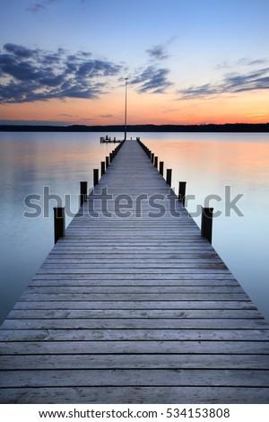 Lake at Sunset, Long Wooden Pier Royalty-Free Stock Photo #534153808