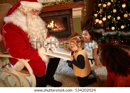 Santa Claus with interesting book having fun with children indoor #534202024