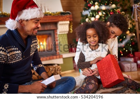 Afro American family with happy little girl opening Christmas present