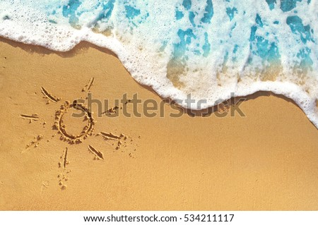 Soft waves with foam blue ocean sea on a golden sunny sandy beach in resort on summer vacation rest. The symbol of the sun drawing on the sand. Background close up #534211117