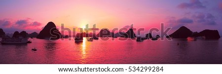 Beautiful purple sunset and rock islands in Halong Bay Vietnam Southeast Asia. Panorama. Junk boat cruise to Ha Long Bay. Exotic scenery. Panoramic view. Landscape Pink sky. Famous landmark of Vietnam #534299284