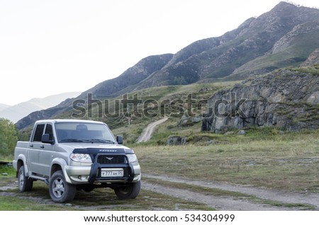 """Altai, Russia - August 03 2016 operating vehicle pickup truck """"UAZ Patriot"""" is parked on the grass at the mountain roads in the Altai 03 Aug 2016. #534304999"""